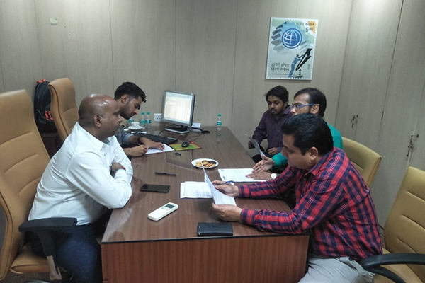 Mr. Sumit Kumar, Preventive Officer, JNCH (far left)  noting some queries arised in the shipping bill given by the member; on his right, Mr. Rajesh Solanki, Superintendant, JNCH interacting with the members. Mr. Pratap Singh Bharda, Executive Officer, EEPC India, Mumbai (right foreground) going through the case, on his right, some members are seen.